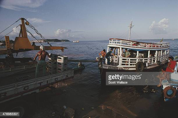 Men unloading crates of Antarctica beer onto a truck from a boat on the Amazon River Brazil 1992