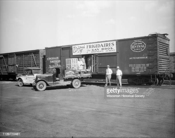Men unloading Frigidaire refrigerators from New York Central/Cincinnati Northern railroad box car to truck, Madison, Wisconsin, August 12, 1928. The...