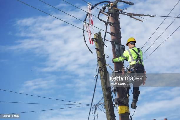 men up pole working on power lines - danger stock pictures, royalty-free photos & images