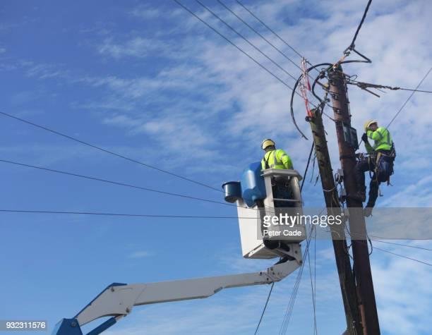 men up pole working on power lines - sicherheitsausrüstung stock-fotos und bilder