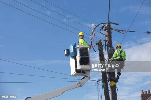 men up pole working on power lines - power line stock pictures, royalty-free photos & images