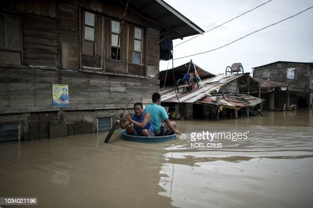 TOPSHOT Men use a basin to cross a flooded street in the aftermath of Super Typhoon Mangkhut at Salonga Compound in Calumpit Bulacan on September 16...