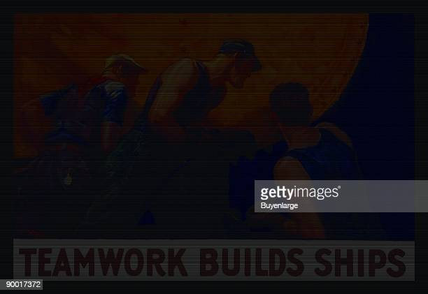 Men use a rivet gun as they build a ship