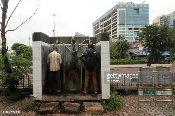 Men use an open air public urinal in New Mumbai India on 08 August 2019