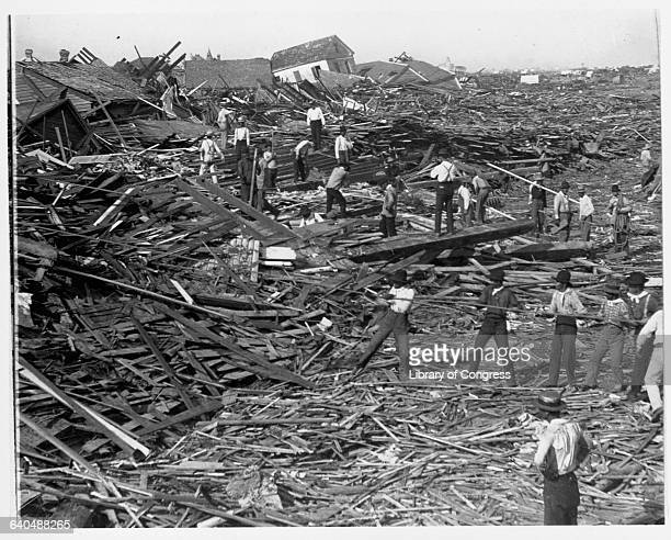 Men use ropes to pull away the debris of houses in order to look for bodies after the Galveston Hurricane of 1900