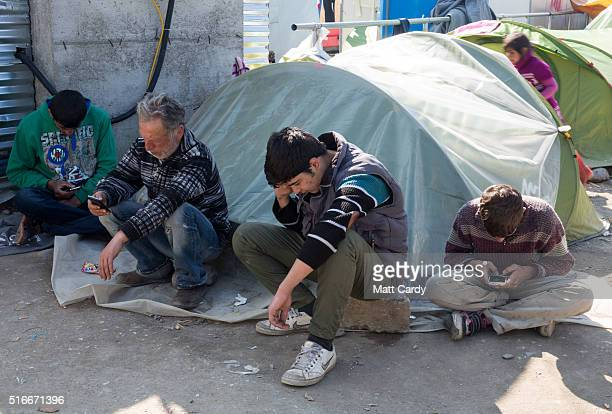 Men use their mobile phones at the Idomeni refugee camp on the Greek Macedonia border on March 20 2016 in Idomeni Greece Thousands of migrants remain...