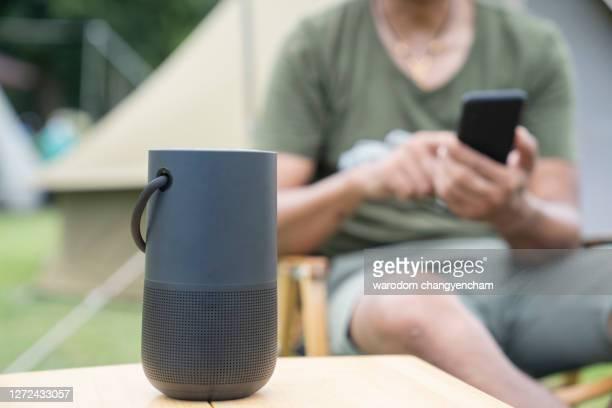 men using a smart speaker with smartphone. - ブルートゥース ストックフォトと画像