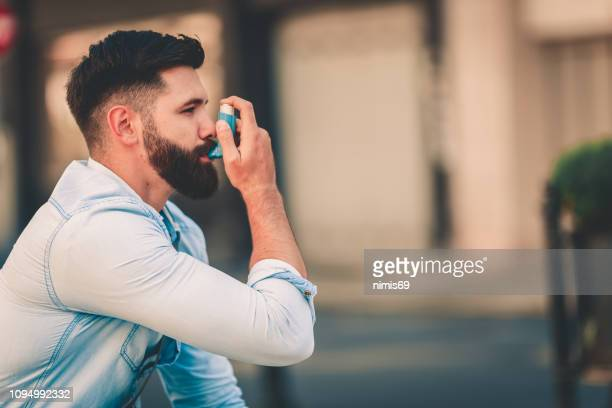 men using asthma inhaler outdoor - copd stock photos and pictures