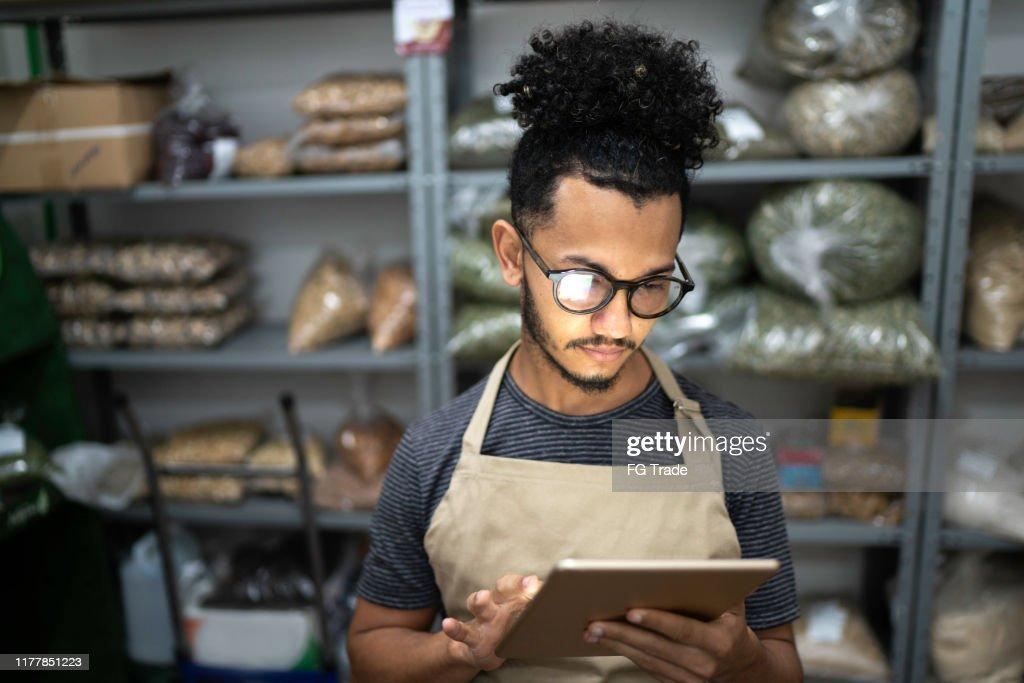 Mannen die digitale Tablet gebruiken in de opslagruimte van een natuurlijke product winkel : Stockfoto