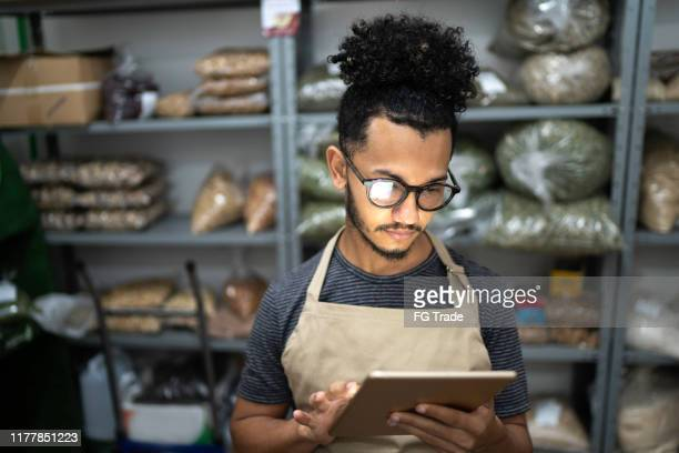 men using digital tablet in storage room of a natural product shop - business owner stock pictures, royalty-free photos & images