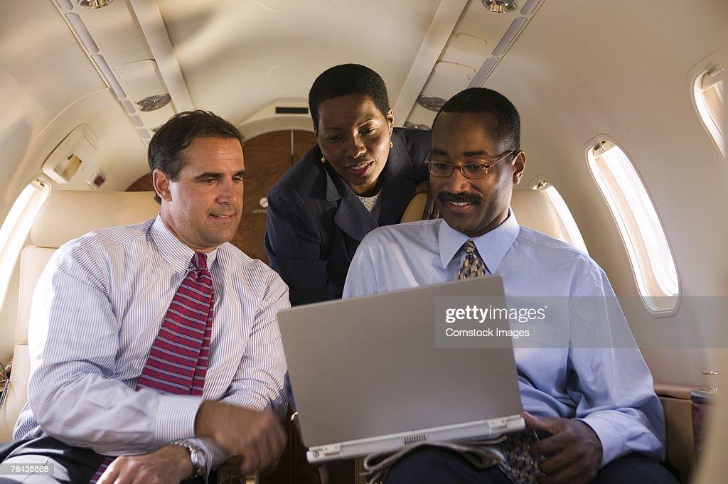 Men using laptop on airplane : Stockfoto