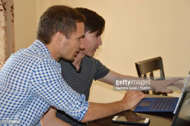Men Using Laptop On Table At Home