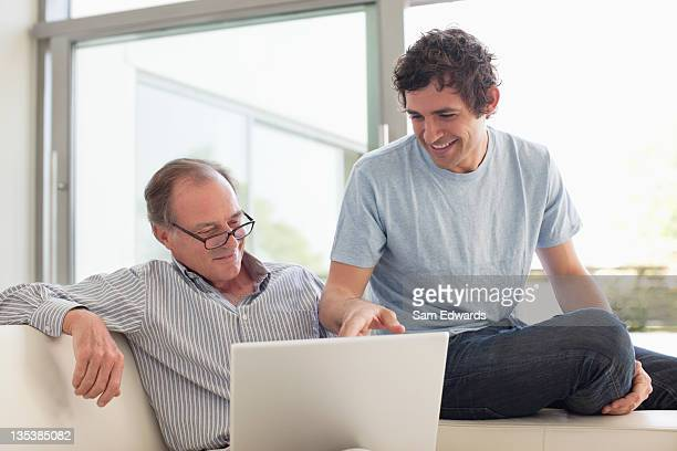 Men using laptop together