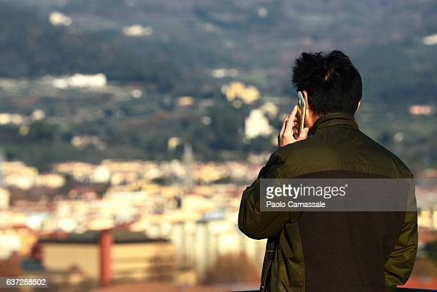 Men using smart phone looking at Florence cityscape, Italy