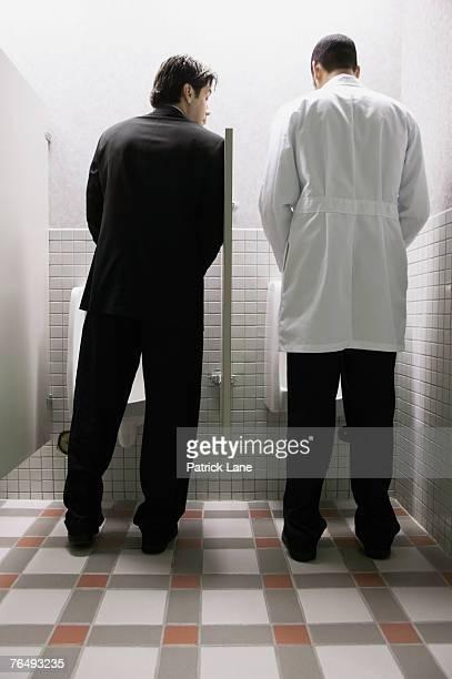 Men using urinals in public bathroom