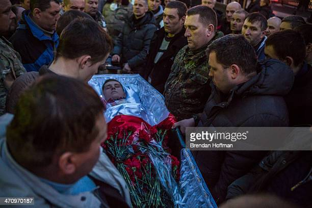 Men view a casket containing the body of an antigovernment protester killed in clashes with police from Independence Square on February 21 2014 in...