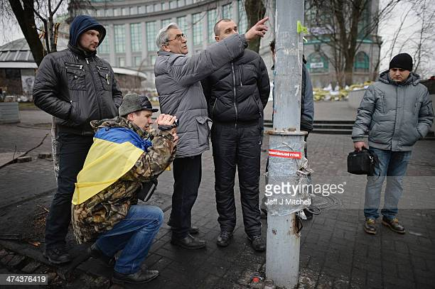 Men view bullet marks on a post where antigovernment protestors were killed in clashes with police near to independence square on February 23 2014 in...