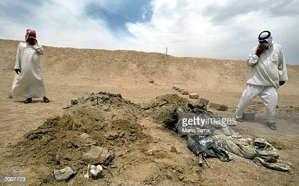 Men view remains dug up from a mass grave at an abandoned military camp May 17 2003 in Habbaniya Iraq According to the Iraqi National Congress the 40...