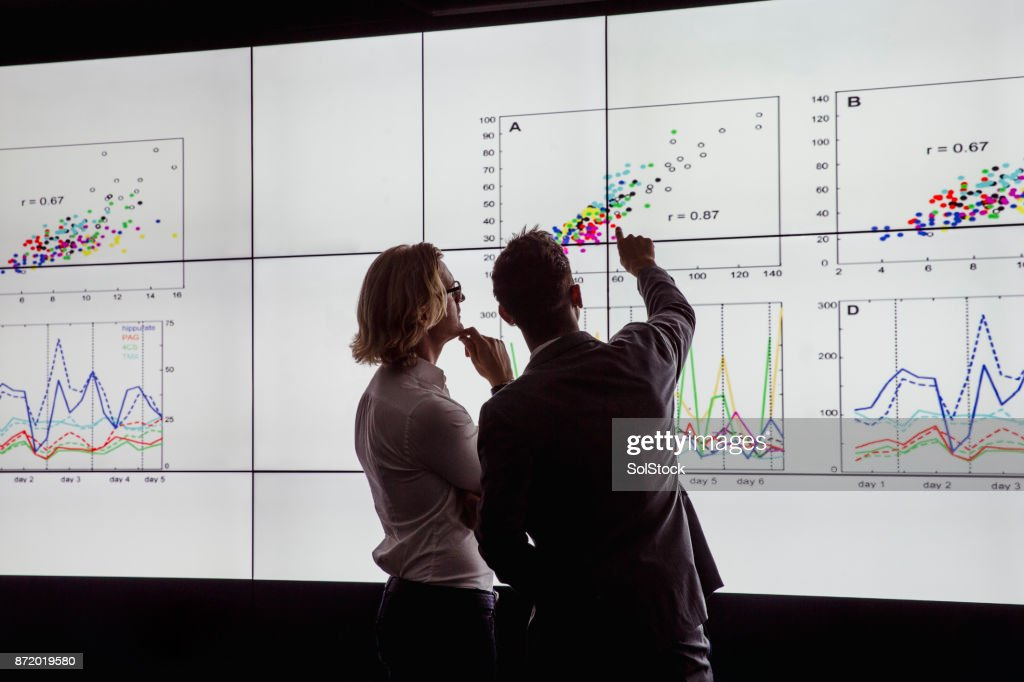Men Viewing a Large Screen of Information : Stock Photo
