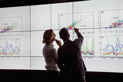Men Viewing a Large Screen of Information 872019580