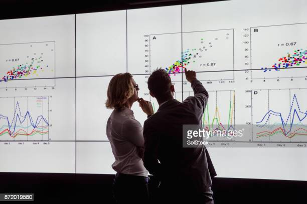 men viewing a large screen of information - ricerca foto e immagini stock