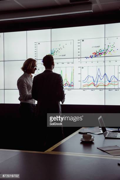 men viewing an oversized computer screen - vertical stock pictures, royalty-free photos & images