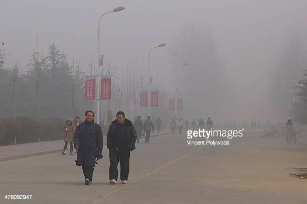 CONTENT] Men wade through the thick air pollution in Anyang City Henan Province China