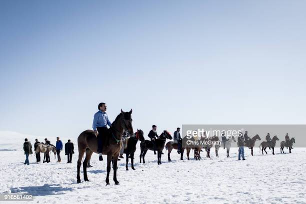 Men wait at the start line before competing in a horse race across the frozen Cildir Lake during the yearly Golden Horse festival on February 10 2018...
