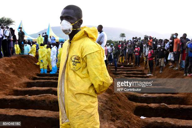TOPSHOT Men wait beside empty graves for the coffins of mudslide victims on August 17 2017 at Waterloo cemetery near Freetown Sierra Leone Sierra...