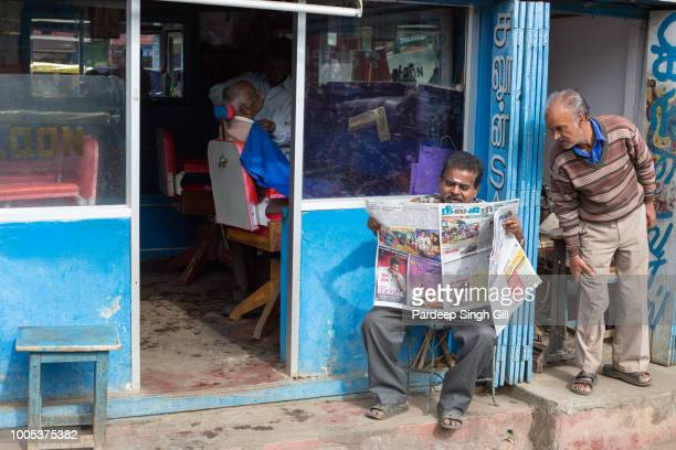 men wait outside of a barber shop in the local market of ooty, tamil nadu. - only men stockfoto's en -beelden