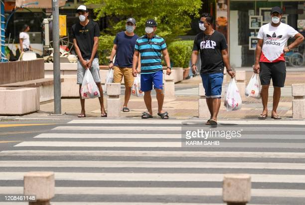 Men wait to cross a street in Dubai on March 28 2020 as the emirate tries to stem the spread of the COVID19 the disease caused by the novel...