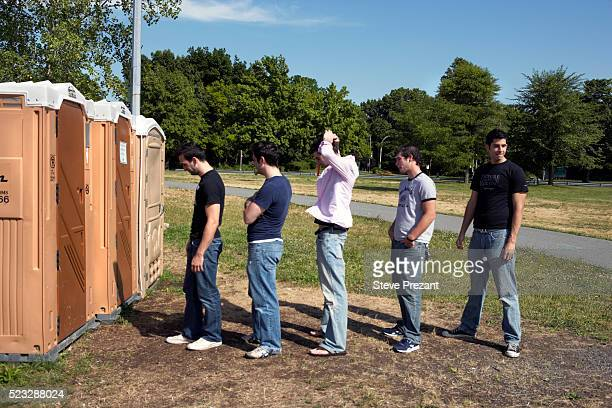 men waiting in line at porta-potty - portable toilet stock photos and pictures