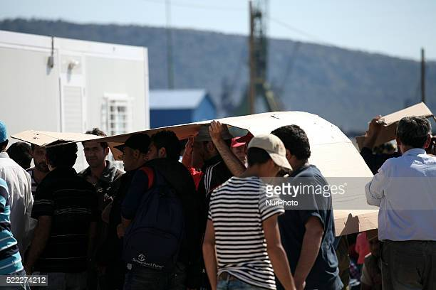 Men waiting in the queue to register while find shadow under cartons Refugee camp in Skaramaga area a port town 11 km west of Athens A large camp is...