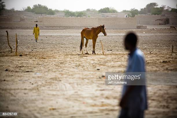 Men walk across the dirt of the central African desert on July 10 2007 around Lake Chad Chad