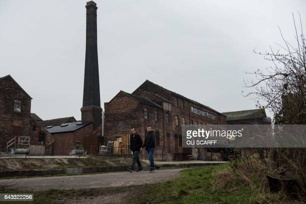 Men walk along a canal path past the site of Middleport pottery which was originally constructed in 1888 in StokeonTrent central England on February...