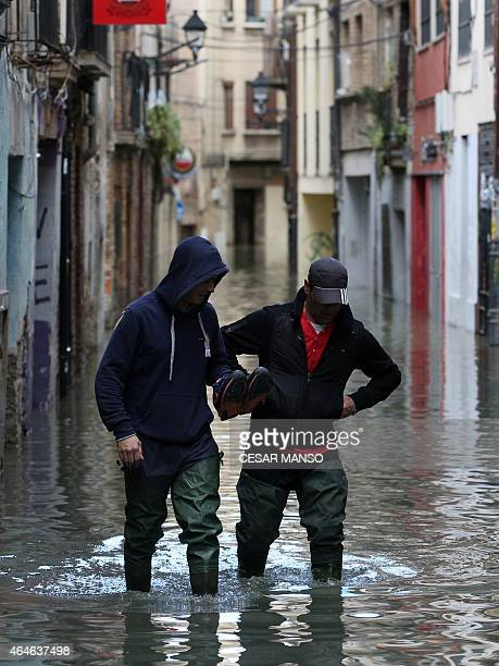 Men walk along a flooded streed after the river Ebro in Tudela broke its banks following heavy rainfall on February 27 2015 AFP PHOTO / CESAR MANSO