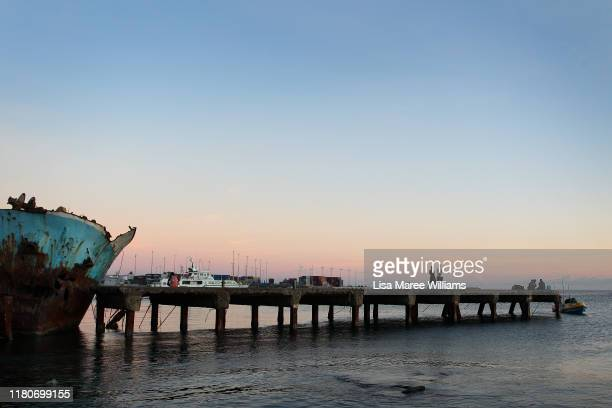 Men walk along a pier at the edge of Honiara Central Markets as performers from the 'Solomon Islands Cultural Group' prepare for the Royal Edinburgh...