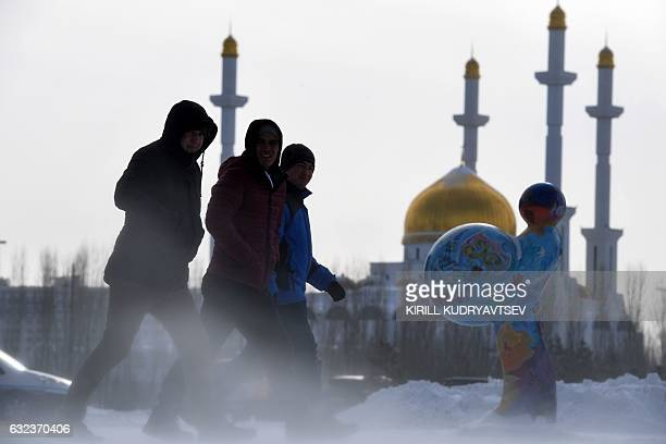 Men walk along a street with NurAstana mosque seen in the background in Astana on January 22 2017 The socalled Astana peace talks set to begin on...