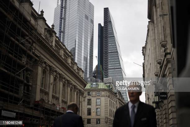 Men walk along streets in the City of London on August 9 2019 Britain's economy unexpectedly shrank in the second quarter official data showed Friday...