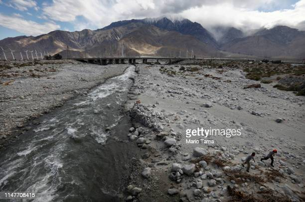 Men walk along the Whitewater River a key water source for the Coachella Valley on May 6 2019 in Whitewater California California's Fourth Climate...