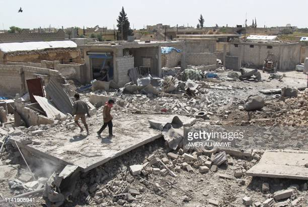Men walk among the rubble of a building that was destroyed during airstrikes by the Syrian regime and their allies near the town of Saraqeb in...