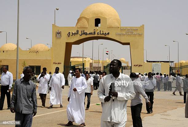 Men walk at the newlyopened EshkeetQastal land crossing between Sudan and Egypt on August 27 2014 According to the Egyptian press Egypt's Minister of...