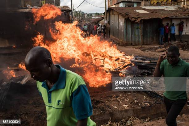 Men walk by a flaming road block created by opposition protestors in the Kawangware slum on October 27 2017 in Nairobi Kenya Protests continued in...