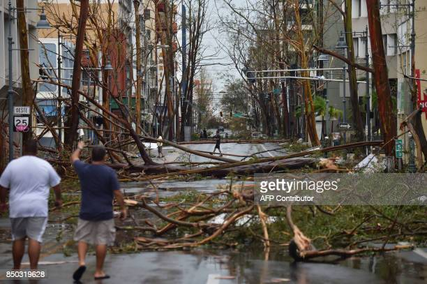 TOPSHOT Men walk damaged trees after the passage of Hurricane Maria in San Juan Puerto Rico on September 20 2017 Maria slammed into Puerto Rico on...