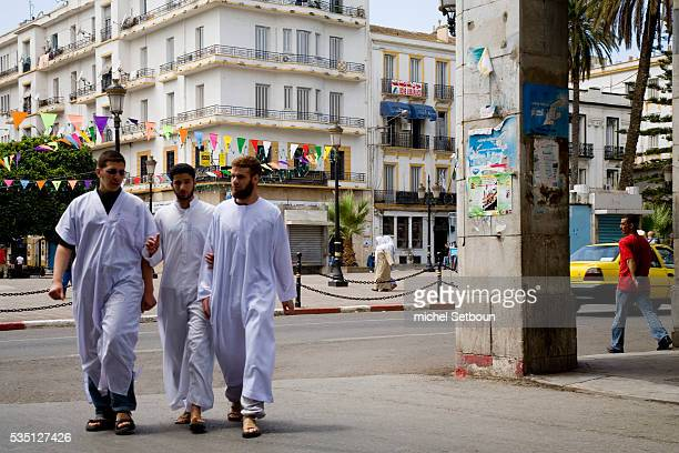 Men walk down Revolution Street formerly Cours Bertagna in the city center