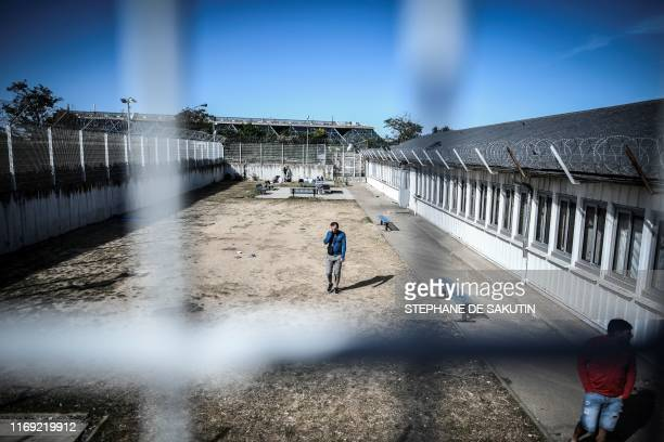 Men walk in a courtyard at the 'Centre de Retention Administrative' , a migrant detention centre in Vincennes, eastern Paris, on September 18, 2019.