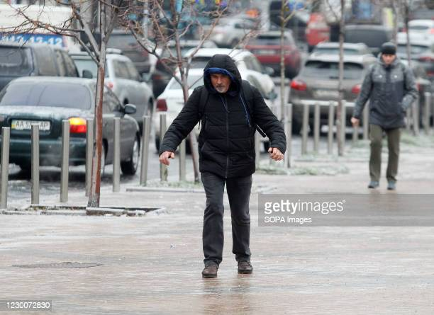 Men walk on a snow covered sidewalk after a heavy rainfall. Kiev was paralyzed, due to worsening weather conditions after freezing rain falls, as a...