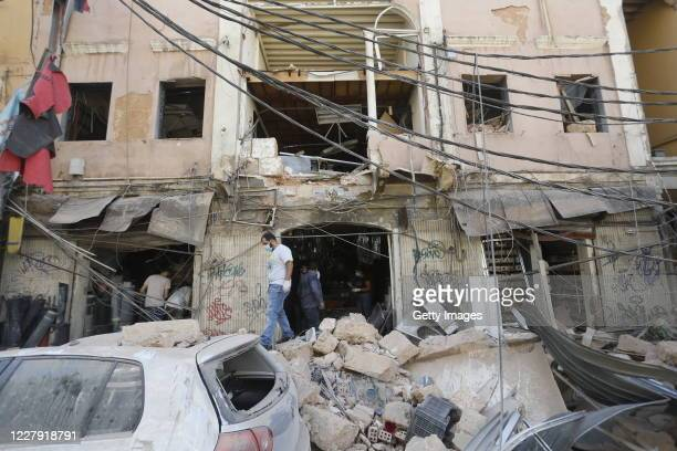 Men walk on debris from a buildings collapsed facade damaged by an explosion a day earlier on August 5 2020 in Beirut Lebanon As of Wednesday morning...