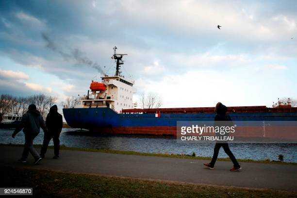 TOPSHOT Men walk on February 26 2018 near the port of Ouistreham northwestern France More than a year after the dismantling of the 'jungle' migrant...