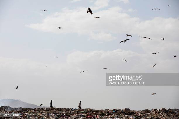 TOPSHOT Men walk on March 12 2017 at main landfill of Addis Ababa on the outskirts of the city after a landslide left at least 30 people dead At...